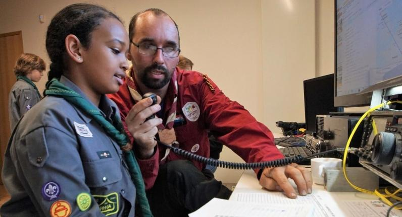 photo: adult leader showing Scout how to use amateur radio